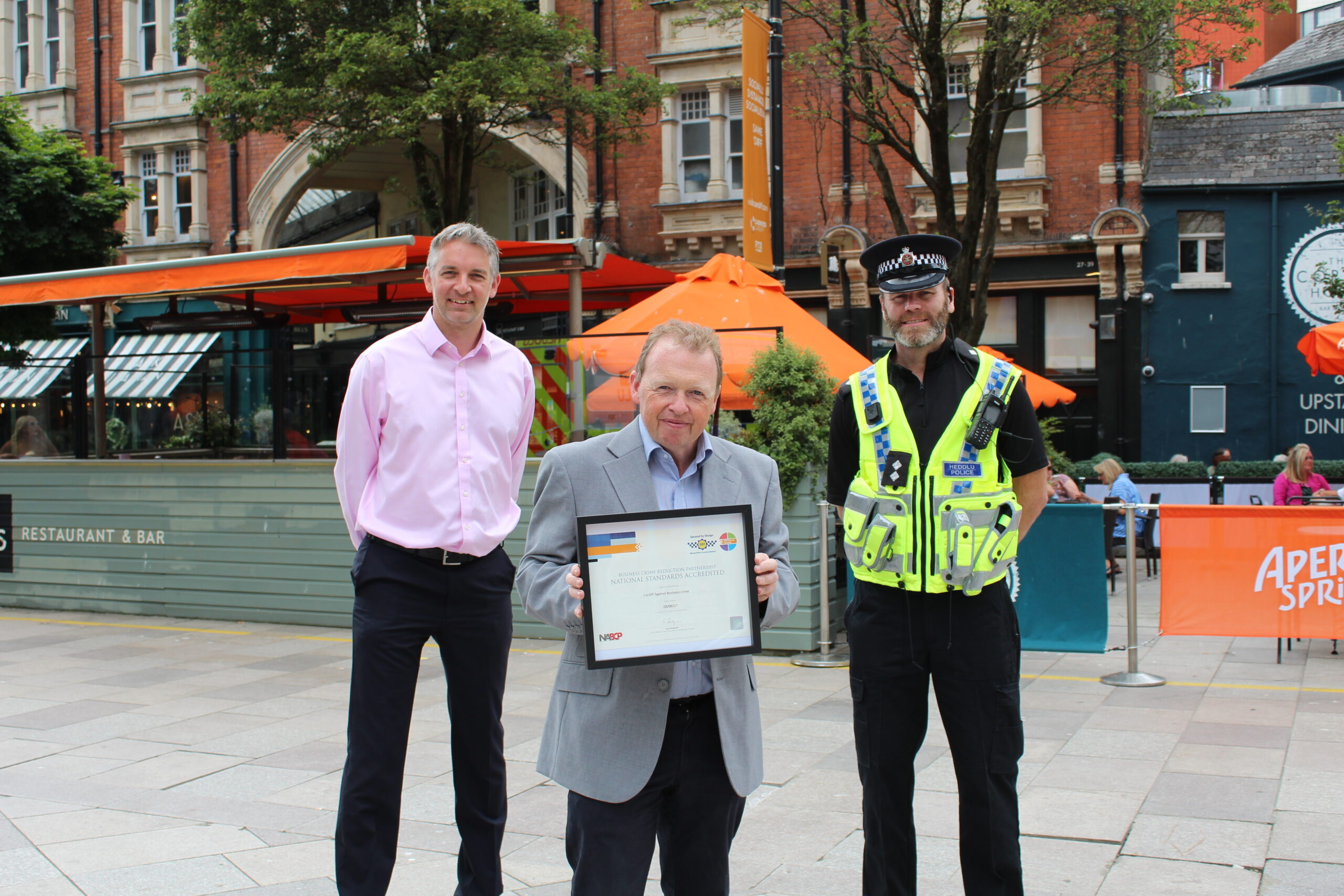 three men standing in Cardiff city centre holding the national standards accreditation certificate